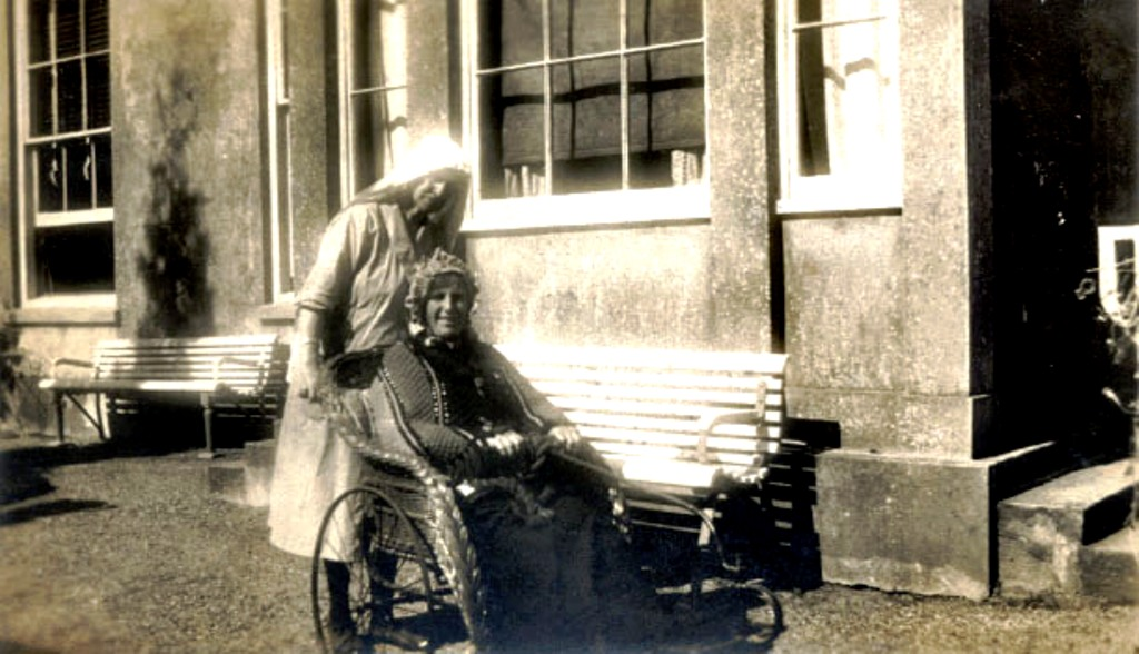 Margaret Parry Thomas (nee Reynolds) in bath chair, pushed by Angelina Thomas (nee Hales)