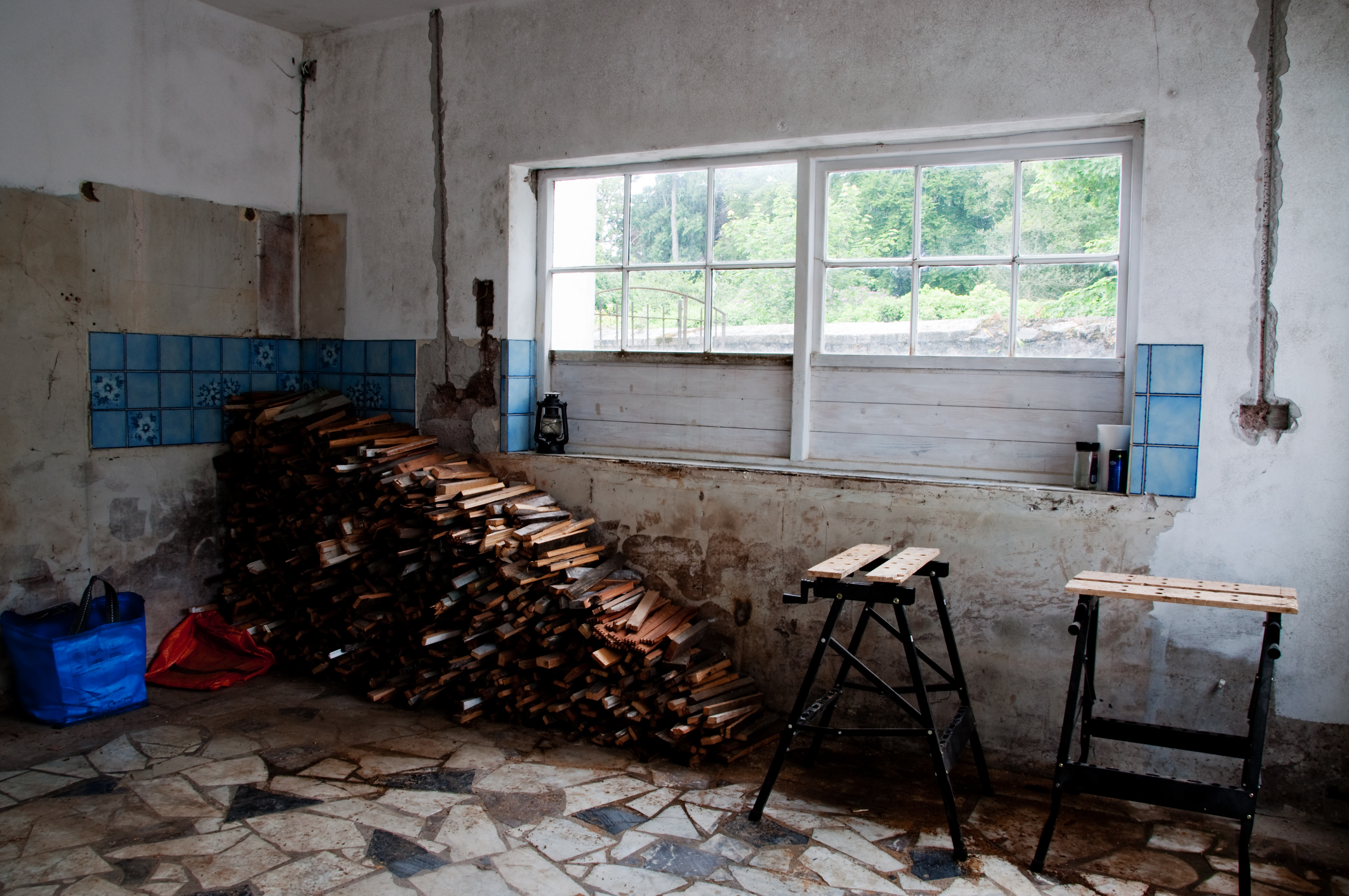 Old guuted kitchen with stored firewood